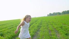 Blond mała śliczna dziewczyna w biel sukni bieg na zielonych ono uśmiecha się i polu Dziecko, dzieciaka bieg w ogrodowym i roześm zbiory wideo