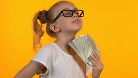 Blond ma?e dziecko trzyma wi?zk? dolary w eyeglasses, pierwszy pieni?dze dobry doch?d zbiory
