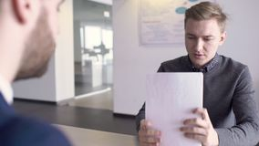 Blond male financial analytic is looking through the contract on the job interview. Young professional is sitting at the table opposite to HR manager in modern stock video