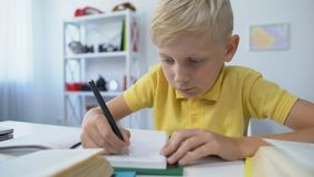 Blond male kid writing hometask in notebook and putting head on table, boredom