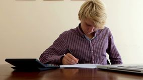 Blond Man Composes Some Document And Looks at His Calculator in Office. A Laborious Young Fair Haired Man Writes Some Document and Looks at a Calculator in His stock video