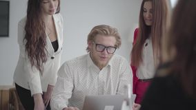 Blond man in glasses sitting in a light comfortable office with netbook at the table. Two girls in formal wear standing. Near and one sitting in front of him stock video footage
