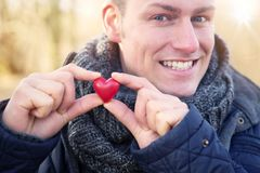Blond man holding a heart in his hands Royalty Free Stock Images