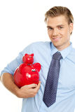 Blond man holding piggybanks Stock Images