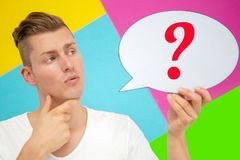 Blond man holding a speech bubble with a question mark stock images