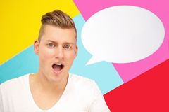 Blond man holding a speech bubble and is shouting royalty free stock photography