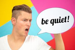 Blond man holding a speech bubble with the words Be Quiet stock illustration