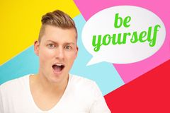 Blond man holding speech bubble with the words Be Yourself. Handsome blond man shouting and holding speech bubble with the words Be Yourself royalty free stock images