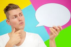 Blond man looking pensive and holding a speech bubble royalty free stock photography