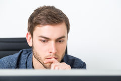 Blond man making decision. Handsome man thinking about business decisions looking at computer screen in his office. Concept of business development Royalty Free Stock Photo