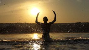 Blond man raises the lake water to entertain at sunset in slo-mo. An optimistic view of a cheery young man who raises his hands with water to entertain and to stock video footage