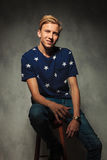 Blond man is resting on a stool and smiles Royalty Free Stock Images