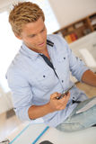 Blond man sitiing on desk looking at smartphone Stock Images