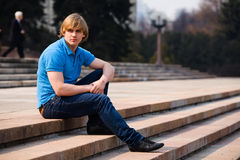 Blond man sitting outdoors Stock Photo