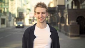 Blond man smiling and pointing at camera. Caucasian blond man wearing white t shirt and black jacket standing in the street, smiling and pointing at camera stock video footage