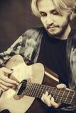 Blond man som spelar den akustiska gitarren Royaltyfri Foto