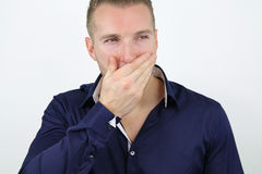 Blond man trying not to laugh Stock Photo