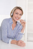 Blond mature businesswoman with headphone at desk at office. Stock Photos