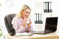 Blond mature businesswoman working on laptop and drinking coffee Stock Photography