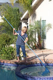 Blond Mature Woman cleaning pool. Smiling middle-aged blond woman cleaning her in-ground pool and spa with a net Royalty Free Stock Photography
