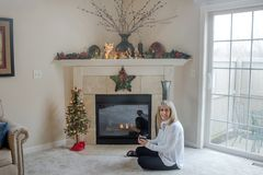 Blond Mature Woman by Fireplace with Christmas Decor. Dayton, Ohio, USA - December 12, 2018: Mature, blond woman sits in front of glass fireplace door looking stock photos