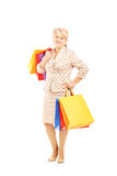 Blond mature woman holding shopping bags Royalty Free Stock Photos