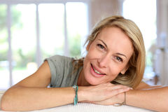 Blond mature woman lying on sofa royalty free stock image