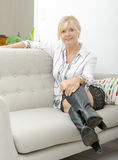 Blond mature woman relaxing in sofa Royalty Free Stock Photo