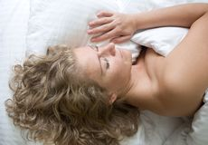 Blond mature woman sleeping in bed royalty free stock photos