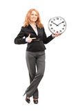Blond mature woman standing and pointing on a wall clock Stock Photos