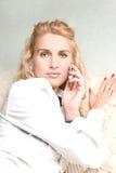 Blond meisje dat op een telefoon spreekt Stock Foto