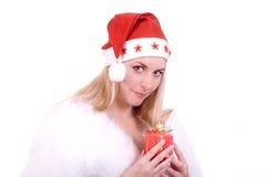Blond meisje in de hoed van de Kerstman met gift Stock Fotografie