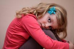 Blond meisje die haar knieën houden royalty-vrije stock foto's