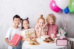 Blond meisje die haar verjaardag met gemengde gerende klasgenoten besteden stock fotografie