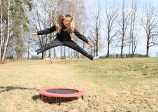 Blond meisje die op trampoline springen Stock Fotografie