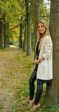 Blond meisje die zich tegen boom bevinden royalty-vrije stock afbeelding
