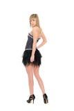 Blond meisje in een korte zwarte rok Stock Fotografie
