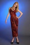 Blond meisje in een lange rode kleding Stock Afbeeldingen