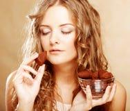 Blond meisje in handeling om een chocoladesuikergoed te eten stock afbeeldingen
