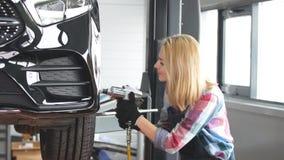 Blond meisje het schroeven autowiel bij de garage stock footage