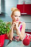 Blond meisje met glas in binnenland van keuken Stock Afbeelding
