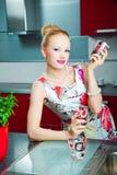 Blond meisje met glazen in binnenland van keuken Stock Foto