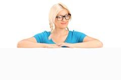 Blond meisje met glazen die achter een paneel stellen Stock Afbeeldingen