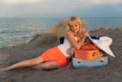 Blond meisje met haar bagage op het strand Stock Afbeelding