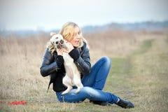 Blond meisje met haar puppy Stock Foto