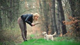 Blond meisje met haar puppy Stock Afbeeldingen