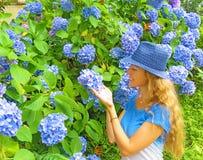 Blond meisje met het lange haar glimlachen die bloemen bekijken die binnen houden royalty-vrije stock afbeelding