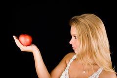 Blond meisje met rode appel stock foto's