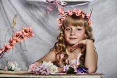 Blond meisje met witte bloemen in haar haar Stock Afbeeldingen