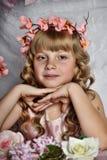 Blond meisje met witte bloemen in haar haar Stock Fotografie